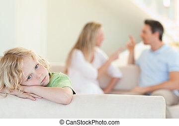 Sad boy with arguing parents behind him - Sad boy with his ...
