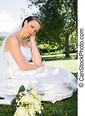 Sad bride with hand on chin in gard