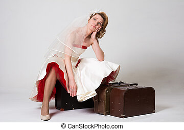 Sad bride with suitcases on white background in studio
