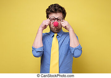 Sad caucasian man dressed as clown crying against a yellow background