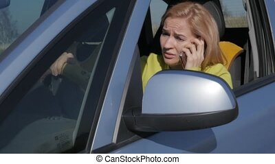 sad charming business womanin a car is calling on mobile...