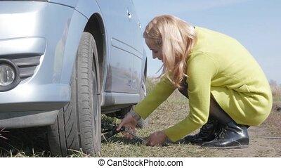 sad charming young woman lifting broken car with jack screw at rural road. 4K