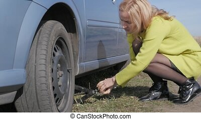 sad charming young woman lifting broken car with jack screw at rural road. slow motion