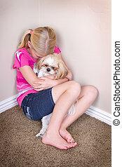 sad child and dog sitting in corner