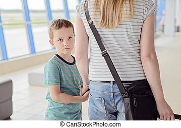 Sad child, boy travelling with his mother
