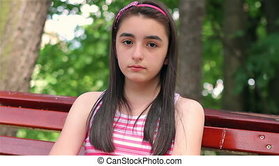 Sad child girl in park