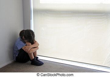 Sad child girl sits in the corner