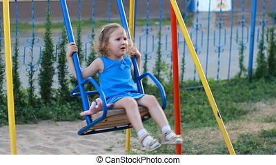 Sad child girl swings on the playground.