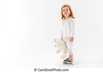 Bewildered little girl is holding toy. She looking at camera with expectation. Portrait. Isolated and copy space in left side
