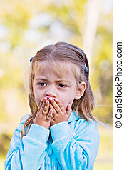 Sad Child - Little girl with hands over mouth and a look of...
