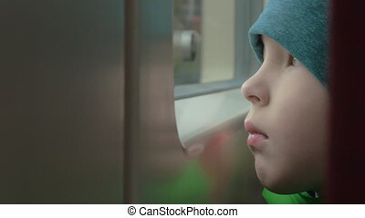 Sad child looking out the window of train