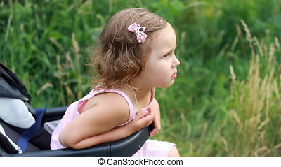 Sad child sits in a stroller and waits for her mother....