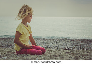 sad child sitting alone in sandy beach near the sea