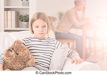Sad child sitting on sofa