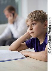 Sad child sitting while his dad working