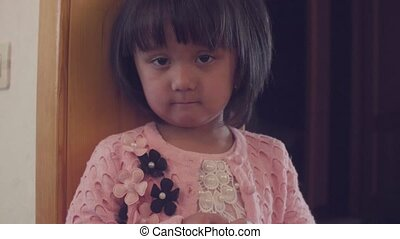 Sad child standing near the door