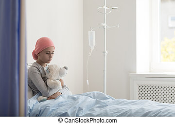 Sad child with cancer hugging plush toy in the hospital with drip