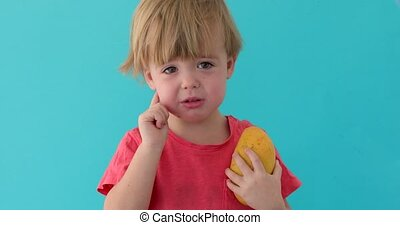 Sad child with mango in hand over blue background
