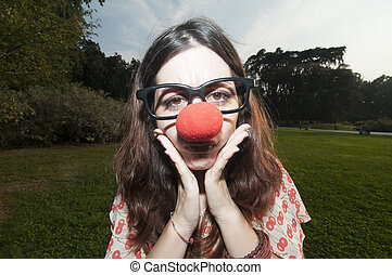 sad clown girl with red nose at the park