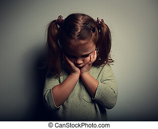 Sad crying alone kid girl on dark background. Closeup...