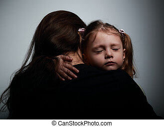 Sad crying daughter hugging her mother with sad face on dark...