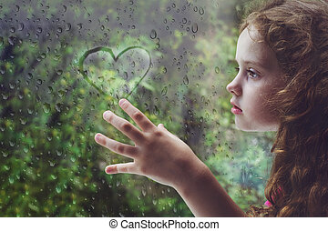 Sad curly little girl looking out the rain drop window
