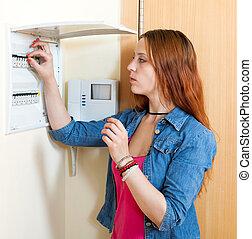 Sad cute woman near power control panel