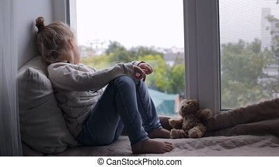 Sad cute young girl sitting on a window sill at home