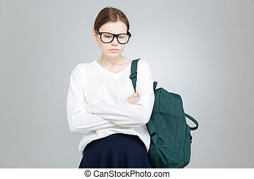Sad depressed girl student in glasses standing with hands folded