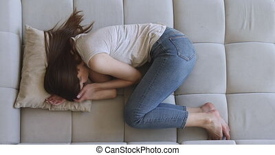Sad depressed young woman lying alone on sofa in fetal position, upset teen girl feeling tired lonely vulnerable and weak trying to sleep hiding thinking of problem suffer from grief trauma, top view