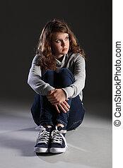 Sad depressed young teenager girl sitting alone - Depressed...