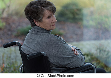 Sad disabled senior woman sitting in a wheelchair