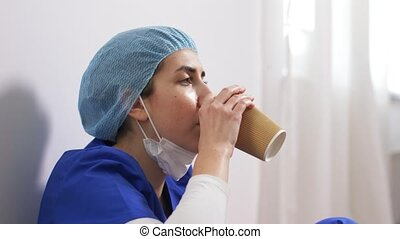 sad doctor or nurse with cup of takeaway coffee