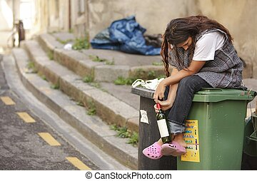 drunk homeless woman sitting on bin and holding botle of wine