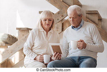Sad elderly couple looking at the photo