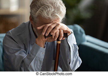 Sad elderly man covering his face with hand holding cane