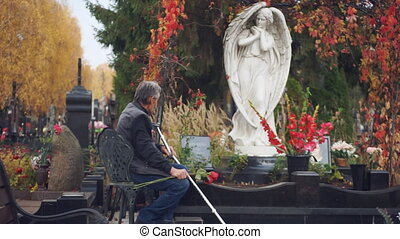 Sad elderly man sitting in a cemetery