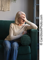 Sad elderly woman crying feeling lonely at home