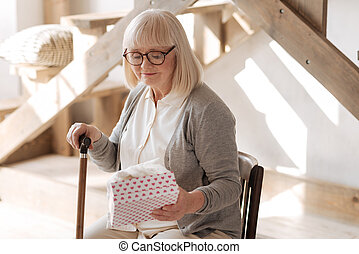 Sad elderly woman looking at the present