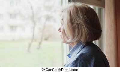 elderly woman looking out the window