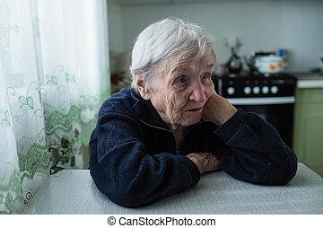 Sad elderly woman portrait near window in the house.