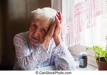 Sad elderly woman sitting in her home.