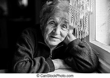 Sad elderly woman sitting near the window. Black-and-white photo.