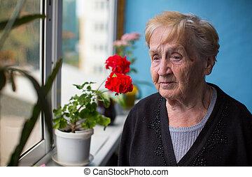 Sad elderly woman stands