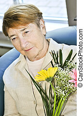 Sad elderly woman with flowers
