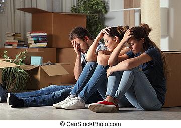 Three sad evicted roommates moving home complaining sitting on the floor