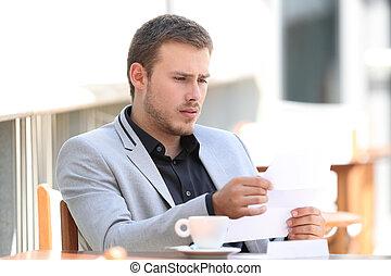 Sad executive reading bad news in a coffee shop