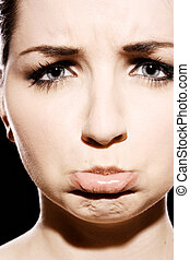 Sad face - A close up of a young woman pulling a sad bratty...