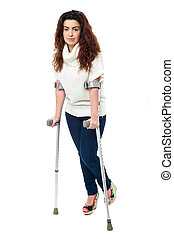 Sad faced woman limping with crutches - n limping with...