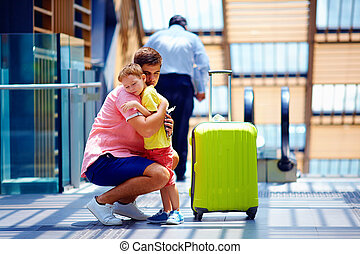 sad father hugging son before leaving in long trip